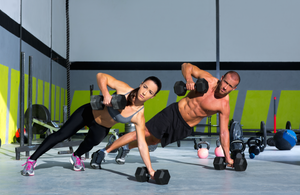 gym couple doing dumbell rows