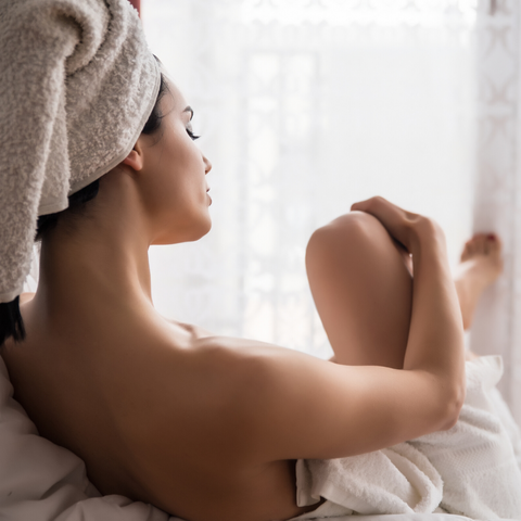 woman applying lotion after bath
