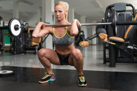 woman doing barbell squat
