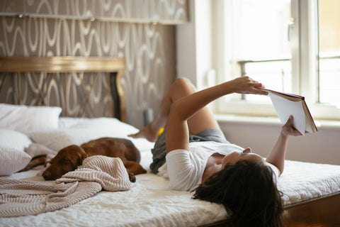 woman-relaxing-in-bed-with-dog