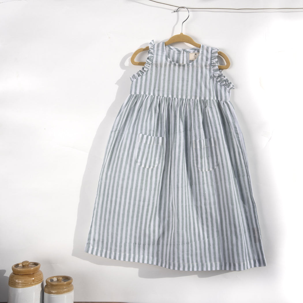 A white cotton mulmul dress for kids with hand-block printed pigeon grey stripes. This mid length dress has front pockets and a back button fastenings accentuated with ruffles on the sleeve, neck and pockets.