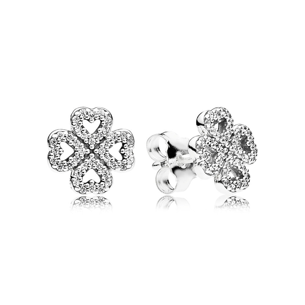 A pair of silver pandora studs with clovers on them.