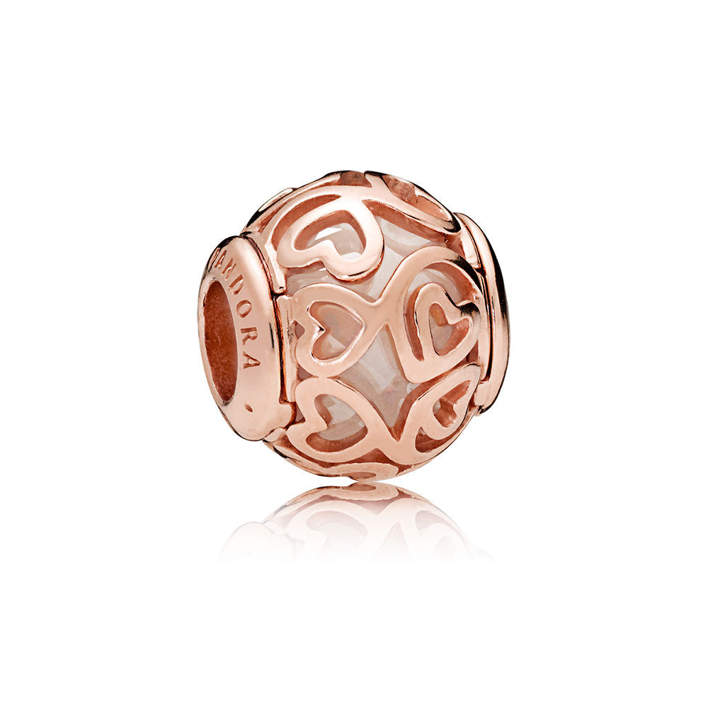 A rose gold charm with a bead in the center by Pandora.