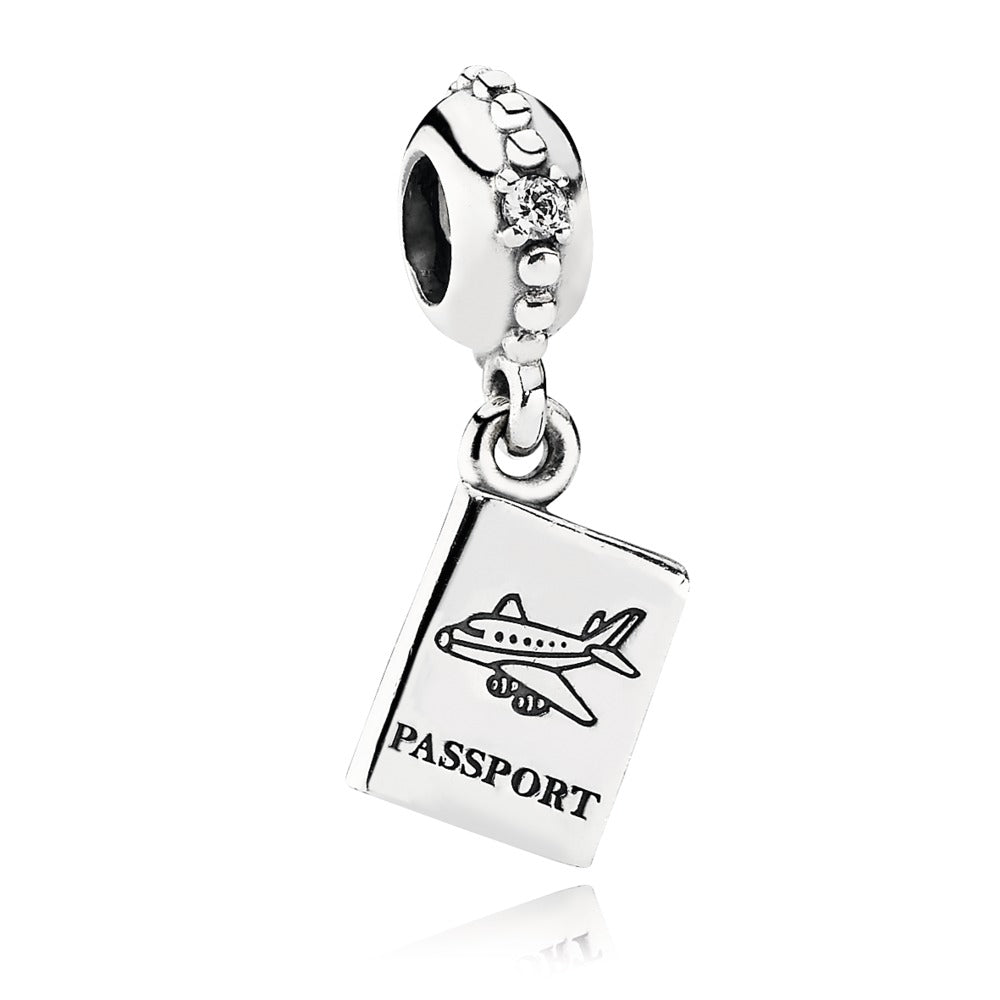 A silver dangle bead showing a passport for travel by Pandora here in Santa Fe.