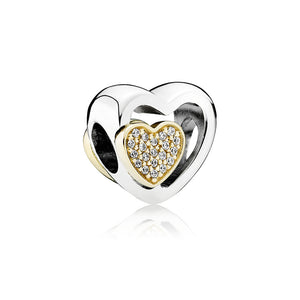 A silver and gold heart charm by Pandora.