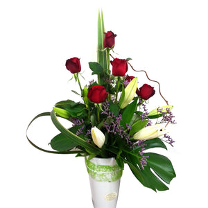 red roses and white lilies accented with fresh greenery delivered in a ceramic vase.