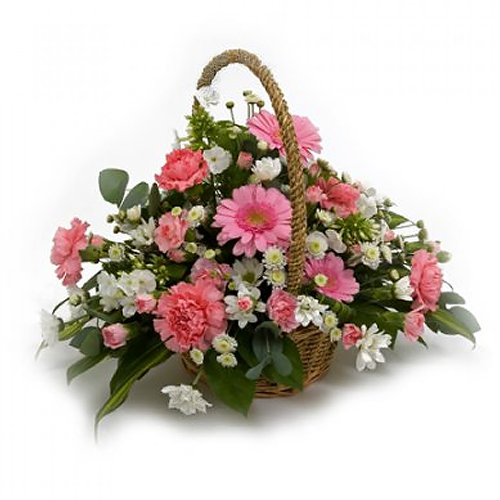 A basket arrangement of fresh cut flowers in pale pink and whites.