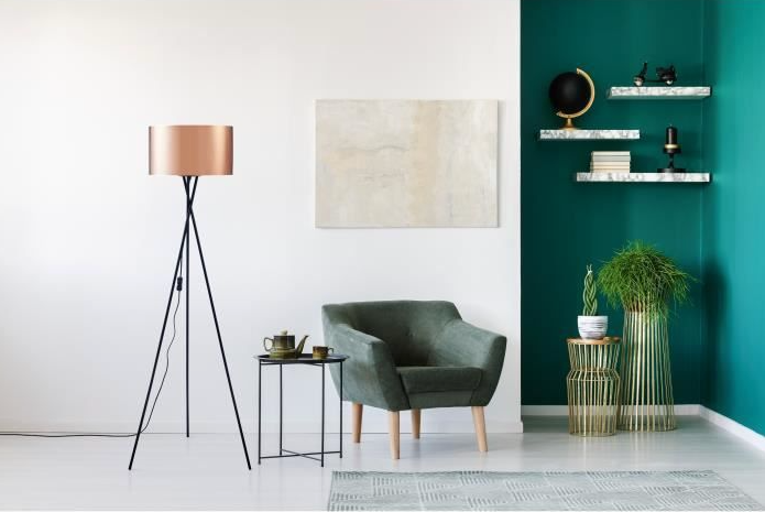 Copper floor lamp with Black metal feet in living room with green armchair and green feature wall