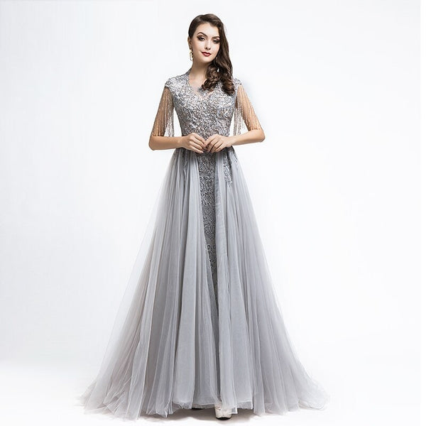"<p style=""font-size: 18px;""><b>ANIKA</b></p><p style=""color:grey"">CRYSTAL EMBELLISHED TASSELLED CAPE GOWN</p>"