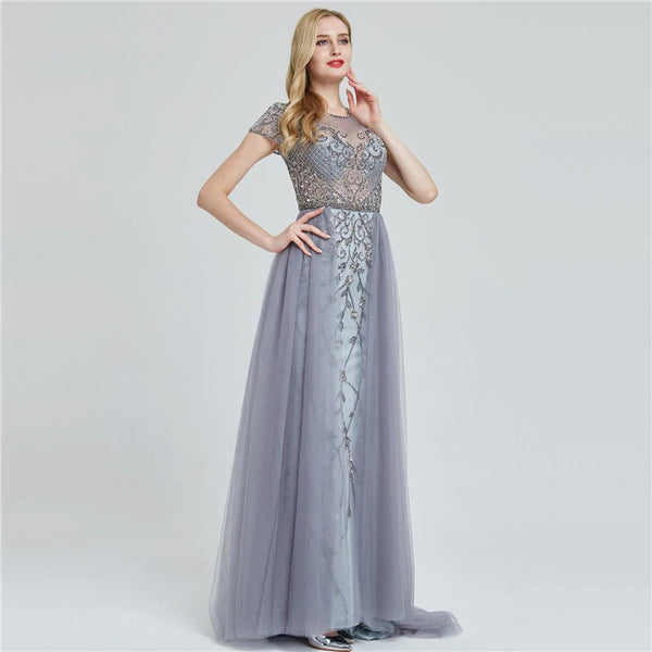 "<p style=""font-size: 18px;""><b>CAMELIA</b></p><p style=""color:grey"">CRYSTAL BEADED FLORAL CAPE GOWN-SILVER/GREY</p>"