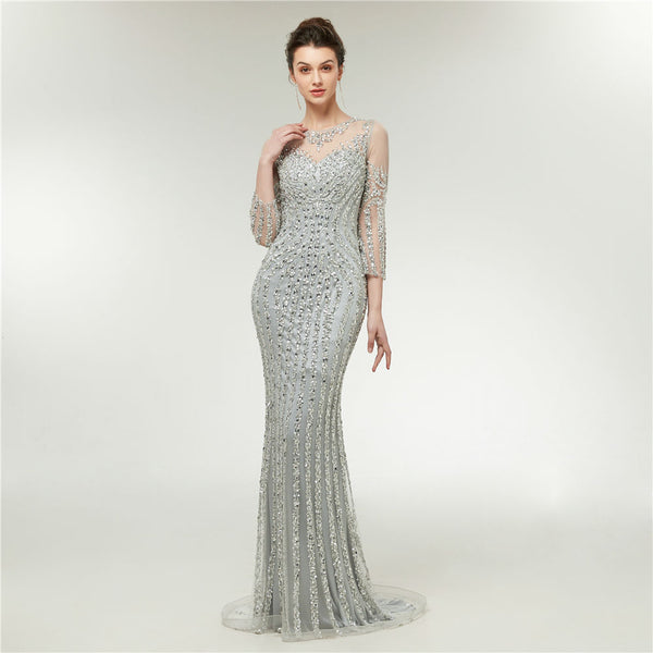 "<p style=""font-size: 18px;""><b>SILVER SHIMMER</b></p><p style=""color:grey"">SEQUIN & CRYSTAL BEADED SHEER BACK MERMAID GOWN</p>"
