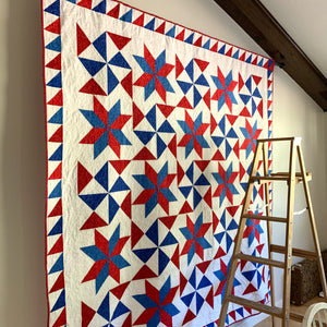Red, White, and Blue Bombs Burst quilt hanging on a wall with a ladder in front of it.
