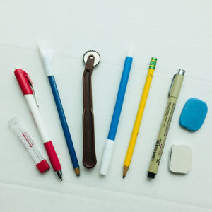 Variety of marking tools including pens, pencils, chalk, and markers.