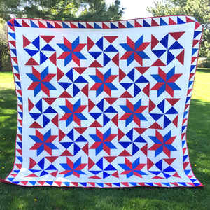 Bombs Bursting Quilt in Red White and Blue in a Park
