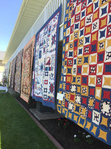 Quilts hanging from a balcony at the quilt show.