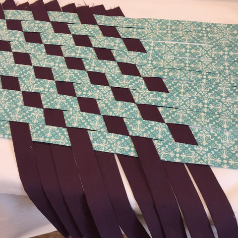 Second set of strips of fabric getting woven together.