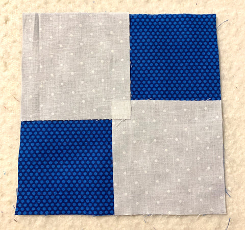 Laying two small squares on top of a large square to make the flying geese