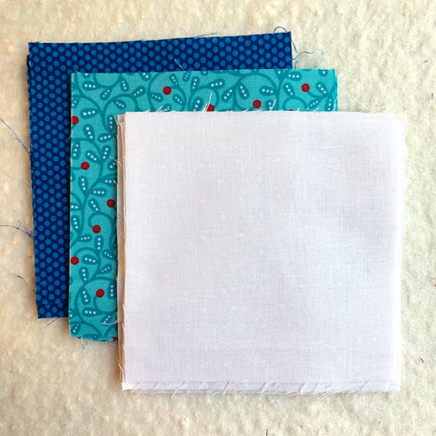Fabric Squares cut out in three colors.