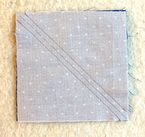 Making half square triangles, two at a time, with white and blue fabric