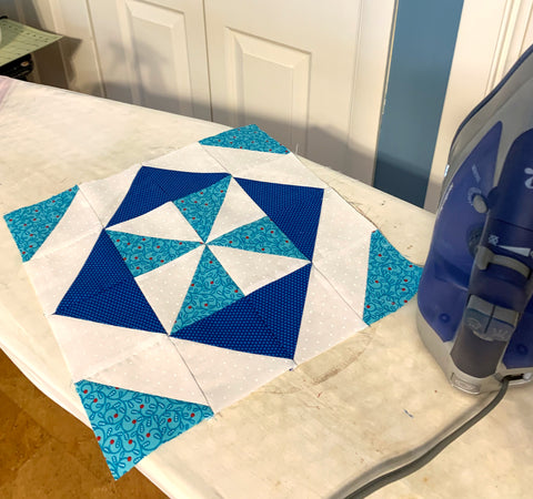 Blue, Teal and White Quilt Block sitting on an ironing board with an iron