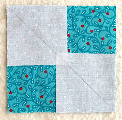 First step for making flying geese. Two small white squares on a larger colored square.