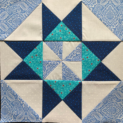 Grandma's Pinwheel quilt block made with half square triangles and quarter square triangles in blue