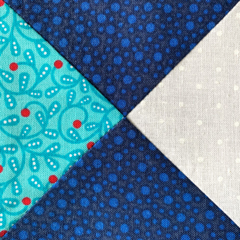Quarter Square Triangle Block in blue, white and teal.