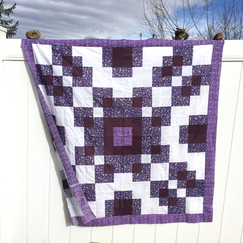 Purple and White Violet Burst Quilt hanging on a white vinyl fence in the backyard