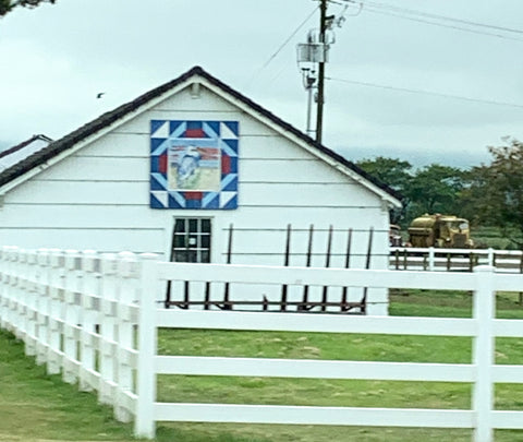 Seagull barn quilt on a white building with a white picket fence