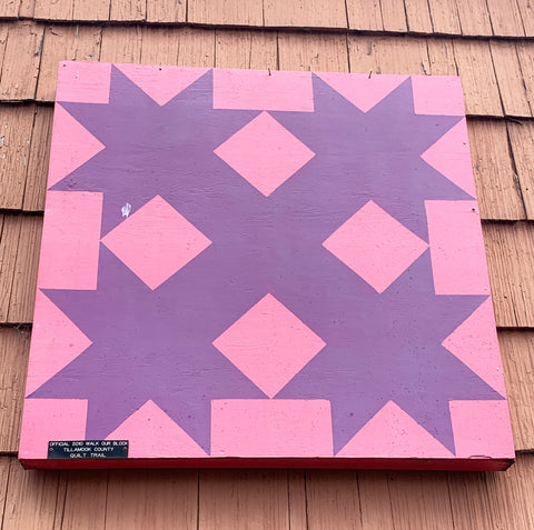 Pink and purple barn quilt hanging on the side of a building.