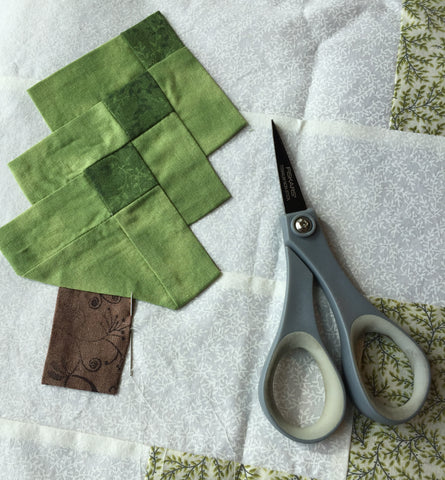 Hand appliquing the Irish woodland trees on to the quilt