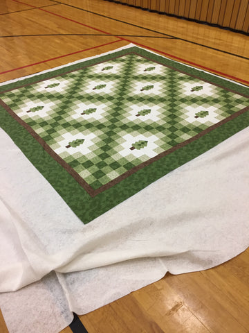 Basting the Irish Woodland quilt together on a gym floor