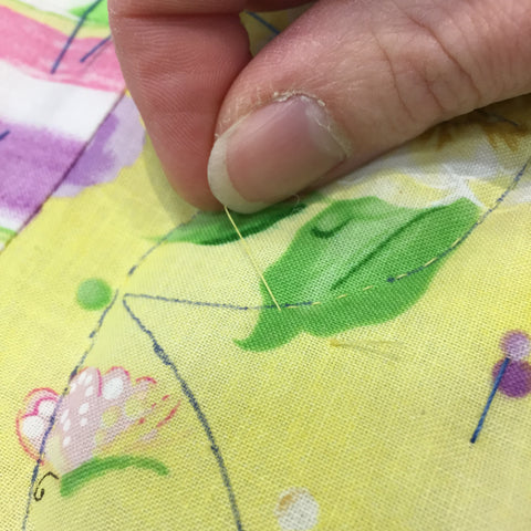 Burying a knot while hand quilting