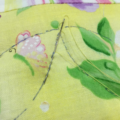 Sewing stitches while hand quilting.