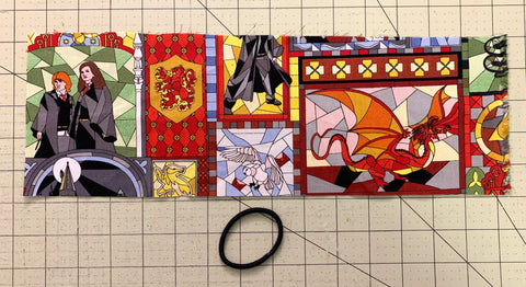 Length of Harry Potter fabric and a hair elastic laying on a cutting mat