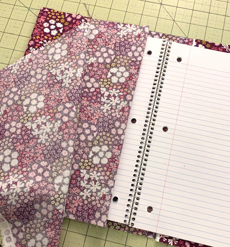 Measuring out the length of the fabric against the notebook