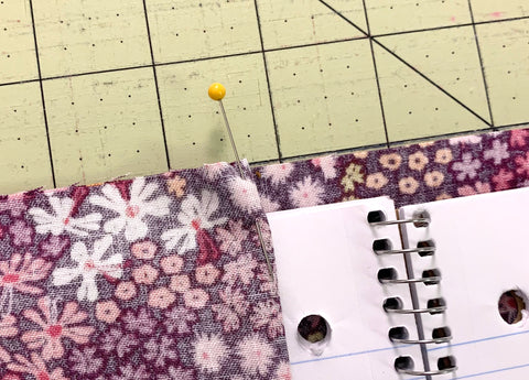 Pinning the fabric in place to be cut