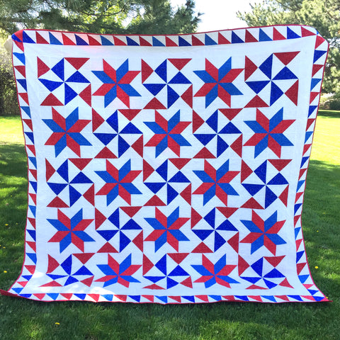 Bombs Bursting Quilt in Red, White, and Blue being photographed in a Park