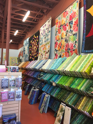 Inside Jewels fabric Stash. Lots of fabric and quilts hanging from the walls.