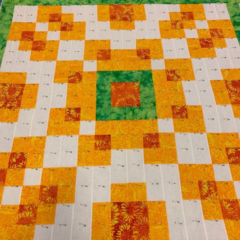 Violet Burst Quilt in bright colors, pin basted together.