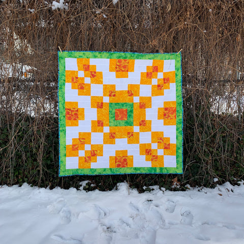 Counterbalance quilt in green, orange, and yellow, hanging off a fence in the snow