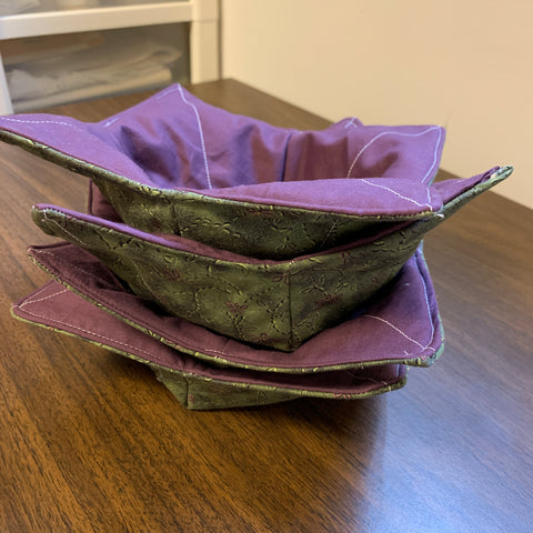 Stack of four purple and green bowl cozies