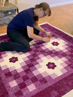 I am sitting on the floor, pin basting my latest quilt project.