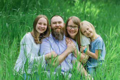 Becky with her family sitting in the grass
