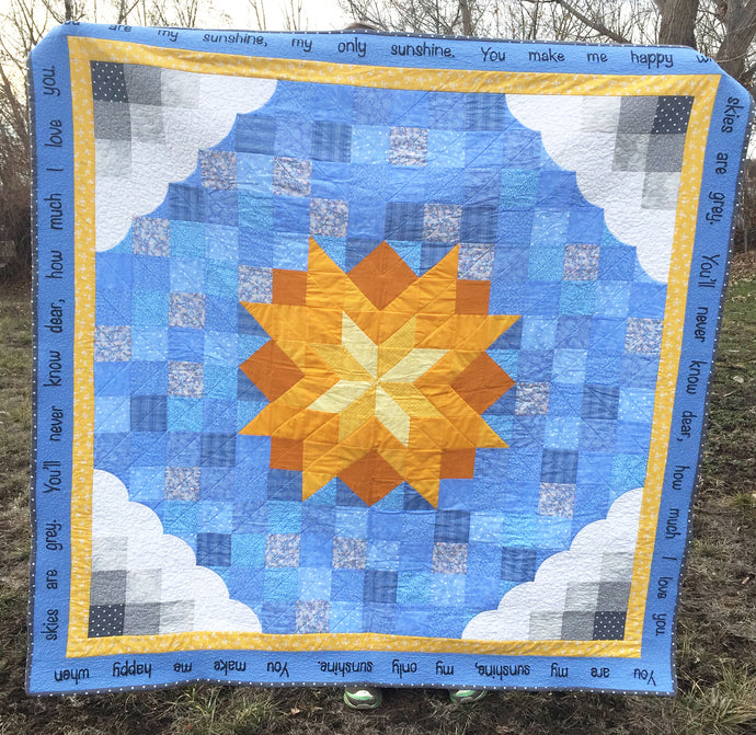 You are My Sunshine Quilt Pattern with grey clouds, blue sky, and a yellow sun