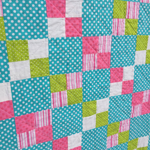 Close up of Alana Quilt Pattern - Easy quilt made in squares with pink, teal, white, and green