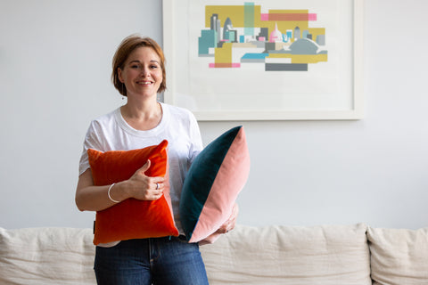 Helen Gilbert, founder of Luxe 39 holding a couple of her luxury velvet cushions