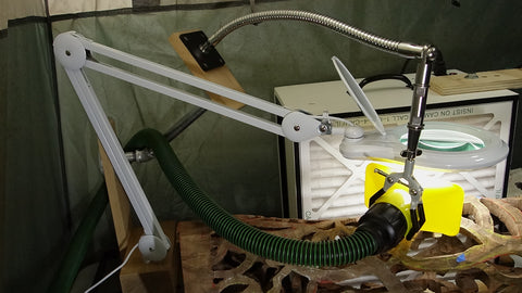 SnakeClamp flexible gooseneck arm and 3-finger clamp supporting dust collector vacuum in a workshop