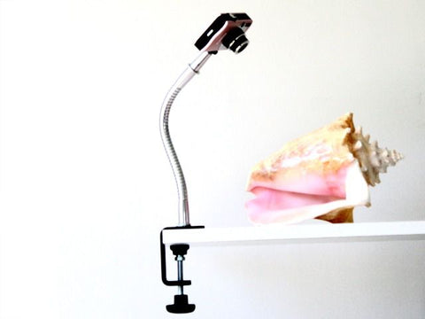 Small camera mounted on flexible gooseneck arm and attached to shelf with table clamp