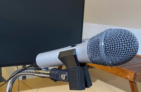 Microphone supported by mic clip attached to flexible gooseneck arm